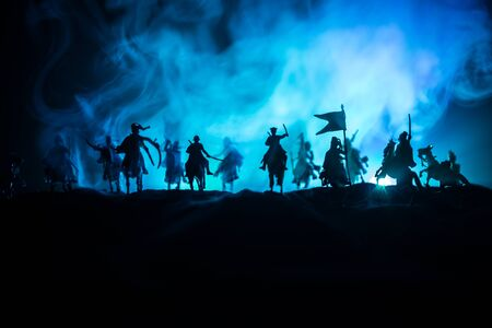 Medieval battle scene with cavalry and infantry. Silhouettes of figures as separate objects, fight between warriors on dark toned foggy background. Night scene. Selective focus Archivio Fotografico - 134749090