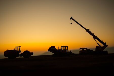 Creative artwork decoration. Construction equipments silhouette on sunset. Loader truck and mobile crane is coming up hill. Construction concept.