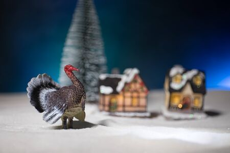 Thanksgiving celebration funny concept. Artwork decoration with Turkey tom statue on snow. Selective focus. Empty space for your text