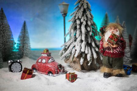 Christmas and New Year holidays concept. Little decorative cute small red car in snow at night. Traditional holiday attributes on snow. Creative artwork decorations. Empty space for your text