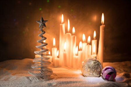 Christmas decorations. Candles in night on snow with traditional winter holiday symbols. Selective focus. Empty space for your text