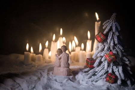 Winter holidays and love concept. Couple doll figures and Christmas decorations on snow with many candles on background. Empty space for your text Stockfoto