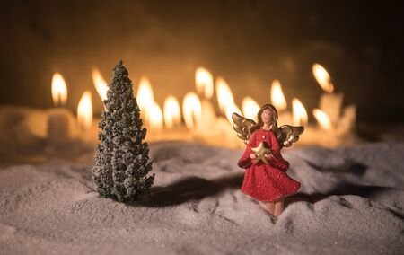 Christmas angel standing on snow with many candles on background. Little white guardian angel in snow. Festive background. Christmas and New Year concept. Selective focus