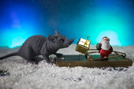 decorative cute brown rat around with a Christmas decor and Santa Claus. The rat is a symbol Of the new year 2020 Stockfoto