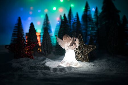 Christmas angel on blur bokeh city lights at night on background. Little white guardian angel in snow. Festive background. Christmas decorations.