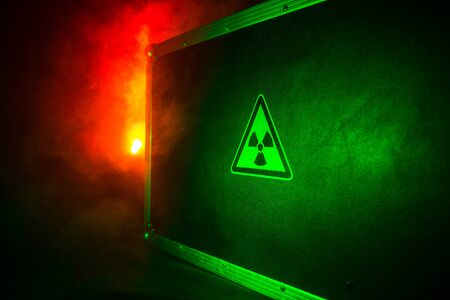 Radioactive (atomic ionizing radiation) danger warning symbol in triangular on a black case. Black suitcase with a sign of radiation hazard. Dark background. Stockfoto