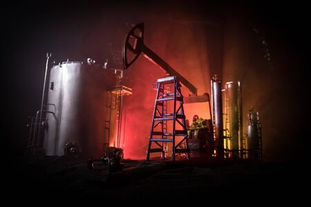 Oil pump and oil refining factory at night with fog and backlight. Energy industrial concept. Selective focus. Artwork decoration. Banco de Imagens