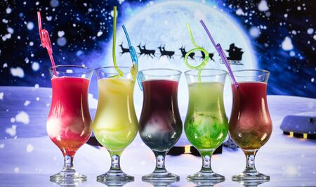 New Year and Christmas party concept. Different tasty cocktails with creative New Year holiday artwork decoration on background. Colorful cocktail in glass. Party club entertainment. Copy space. Banco de Imagens