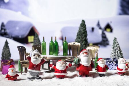 Funny Christmas concept. Creative artwork decoration. Alcoholic Santa Drinking a Wine Bottle on snow. Drunk santas have a party. Selective focus.