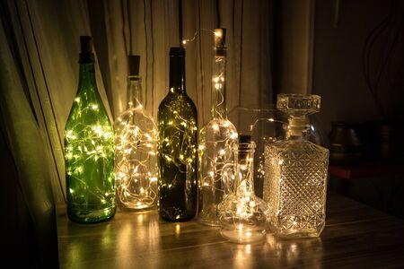 Lights garland in a glass bottle on a dark background. Warm interior design