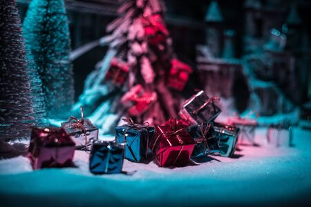 Miniature of winter snowy scene with train on bridge, medieval castle and lantern. Holiday attributes. Night scene. New Year and Christmas concept. Selective focus Banco de Imagens