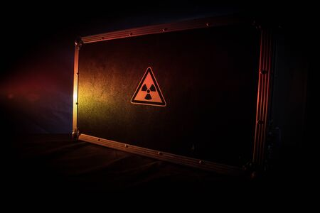 Radioactive (atomic ionizing radiation) danger warning symbol in triangular on a black case. Black suitcase with a sign of radiation hazard. Dark background. 写真素材