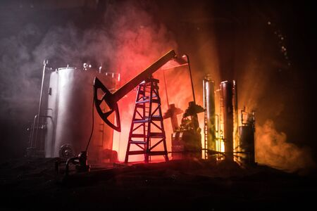 Oil pump and oil refining factory at night with fog and backlight. Energy industrial concept. Selective focus. Artwork decoration. Stock Photo