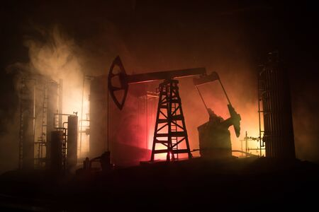 Oil pump and oil refining factory at night with fog and backlight. Energy industrial concept. Selective focus. Artwork decoration. 版權商用圖片