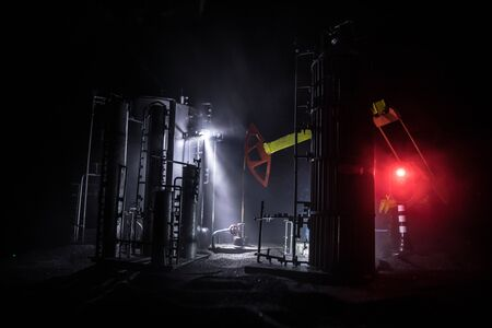 Oil pump and oil refining factory at night with fog and backlight. Energy industrial concept. Selective focus. Artwork decoration. Stockfoto