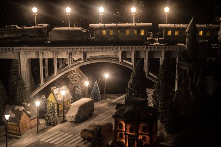 Miniature of winter snowy scene with train on bridge, medieval castle and small city. Holiday attributes. Night scene. New Year and Christmas concept. Creative artwork mini on table decoration Stock Photo