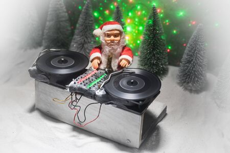 Christmas and New Year club concept. Dj mixer with headphones on snow. Santa Claus is mixing on turntable. Creative miniature artwork decoration on snow. Stock Photo