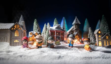 Christmas and New Year holidays concept. Little decorative cute small houses in snow at night. Traditional holiday attributes on snow. Creative artwork decorations. Empty space for your text
