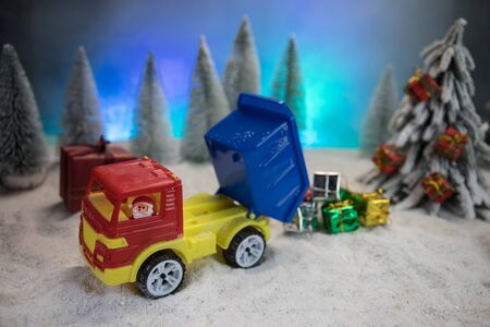 Miniature Gift Box by Forklift Machine on snow ,Determined Image for Christmas Holiday and Happy New Year Gift Celebration concept. Empty space for text