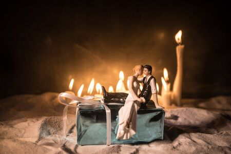 Winter holidays and love concept. Couple doll figures and Christmas decorations on snow with many candles on background. Empty space for your text Stock fotó