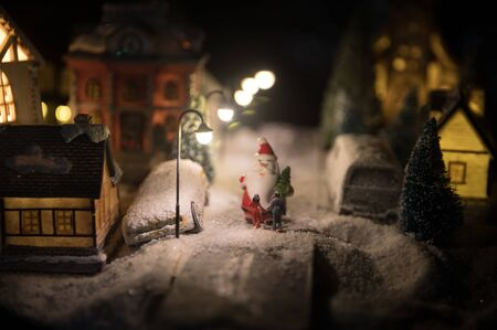 Little decorative cute small houses in snow at night in winter, Christmas and New Year miniature house in the snow at night with fir tree. Holiday concept. Selective focus