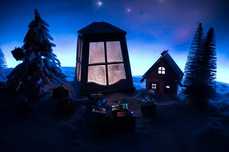Christmas lantern on snow with fir tree and moon. Festive dark background. New Years still-life postcard lamp covered in snow with glowing candle at night. Holiday concept. Artwork