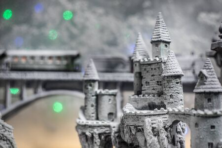 Miniature of winter snowy scene with train on bridge, medieval castle and lantern. Holiday attributes. Night scene. New Year and Christmas concept. Selective focus Stock fotó