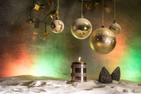 Christmas decoration with burning candles on a dark background. Christmas ornaments over dark golden background with lights. Creative artwork decoration.