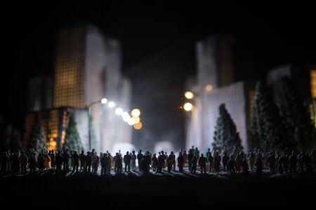 Little miniature city with road and lights. Decorative cute small houses in snow at night in winter. Creative Holiday concept. Christmas and New Year attributes decorated composition.