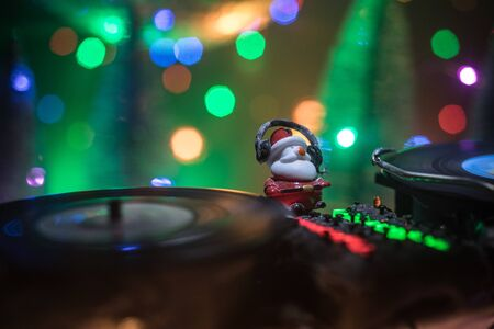 Christmas and New Year club concept. Dj mixer with headphones on snow. Santa Claus is mixing on turntable. Creative miniature artwork decoration on snow. Stock fotó