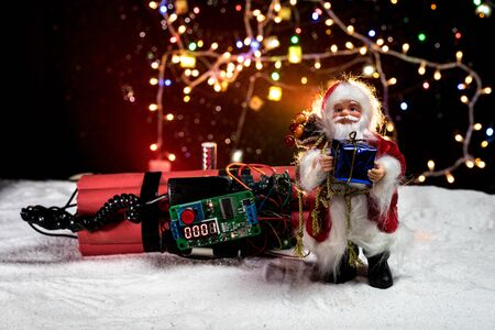 Christmas and New Year funny concept. Time bomb (dynamite) on snow with holiday decor and santa. Timer counting down and New Year is coming. Selective focus