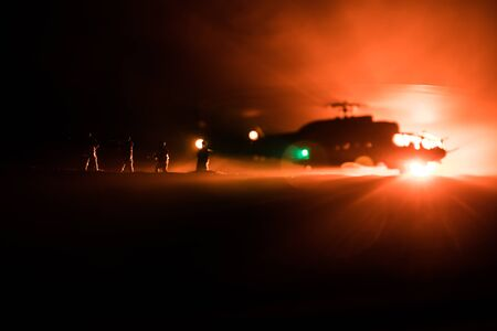 Silhouette of military helicopter ready to fly from conflict zone. Decorated night footage with helicopter starting in desert with foggy toned backlit. Selective focus. War concept Banque d'images