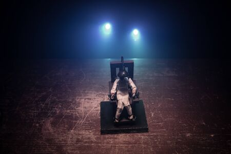 Death penalty electric chair miniature on dark. Creative artwork decoration. Image of an electric chair scale model on a dark backgorund