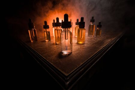 Vape concept. Smoke clouds and vape liquid bottles on dark background. Light effects. Useful as background or vape advertisement or vape background. Selective focus Banque d'images