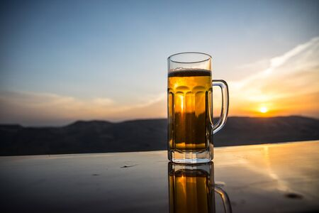 Glass of beer on a beach at sunset. Cooling summer drink concept. Close Up of A Glass of Draught Beer with the Bokeh of Sunlight Background, Soft Focus
