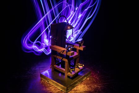 Miniatura de silla eléctrica de pena de muerte en la oscuridad. Decoración de obras de arte creativas. Imagen de una maqueta de silla eléctrica sobre un fondo oscuro