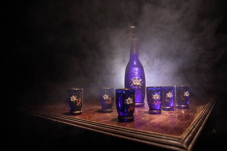 A beautiful blue carafe with vodka stands on a wooden table with glasses. Dramatic toned foggy background with light. Selective focus. Club drink concept.