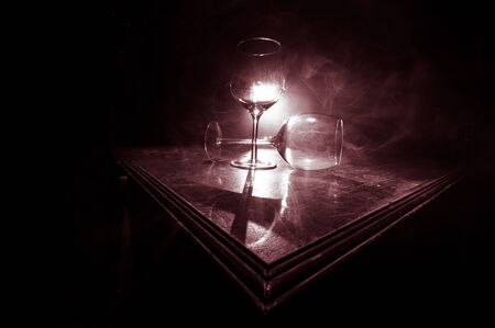 Empty Goblet of wine on wooden table with beautiful toned lights on background. Glasses of wine on dark background. Selective focus. Club drink concept