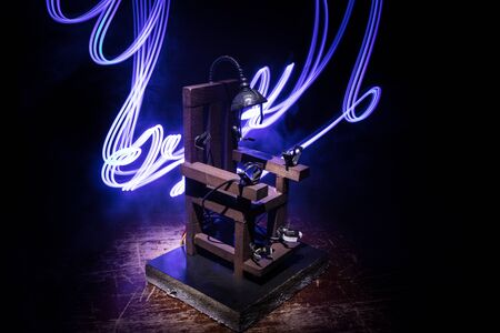 Death penalty electric chair miniature on dark. Creative artwork decoration. Image of an electric chair scale model on a dark backgorund Archivio Fotografico