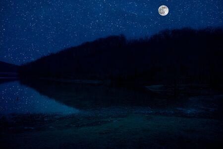 Landscape of gorgeous full moon over the snow-capped mountains reflected in the lake or mysterious night sky with full moon