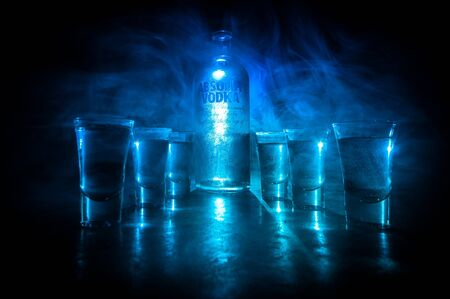 BAKU, AZERBAIJAN - FEB 09, 2020: Absolut Vodka is a brand of vodka, produced near Ahus, in Sweden. Owned by French group Pernod Ricard. Bottle of vodka on wooden table with dark toned foggy background.