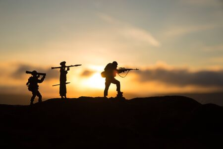 Military soldiers silhouettes with bazooka and rpg. War Concept. Military silhouettes fighting scene on war fog sky background, Mojahed with rpg and us soldier with bazooka at sunset. Attack scene Imagens