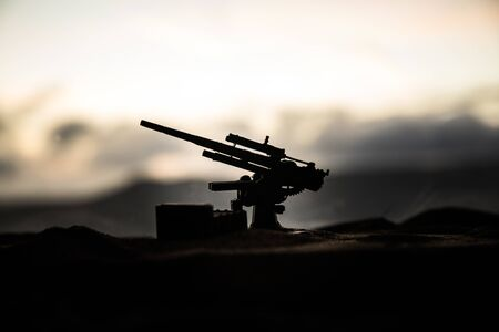 Silhouette of anti-aircraft cannon on battlefield during sunset time. Creative artwork table diorama. Selective focus. , World War Soldiers Silhouettes Below Cloudy Skyline at sunset. Stock Photo