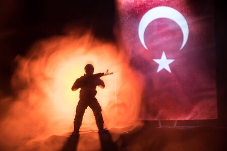 Turkish army concept. Silhouette of armed soldier against a Turkish flag. Creative artwork decoration. Military silhouettes fighting scene dark toned foggy background. Selective focus