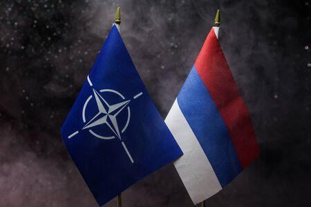 Russia and Nato small flag on dark background. Concept of crisis of war and political conflicts between nations. Selective focus Archivio Fotografico