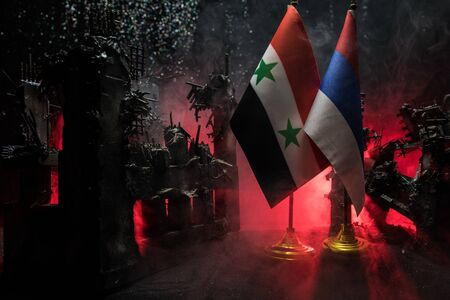Closeup, flags of Russia and Syria against destroyed city at night. Decorated diorama. Concept of crisis of war and political conflicts between nations. Selective focus Standard-Bild