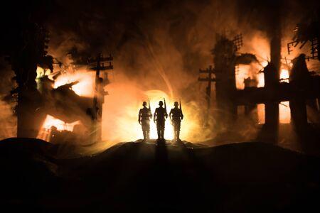 Kriegskonzept. Militärische Silhouetten Kampfszene auf Kriegsnebel Himmelshintergrund, Weltkrieg Soldaten Silhouette unter bewölkter Skyline in der Nacht. Schlacht in der zerstörten Stadt. Selektiver Fokus Standard-Bild