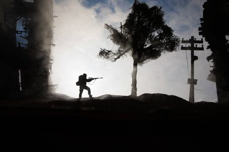 Army sniper with large caliber rifle standing in the fire and smoke. War Concept. Battle scene on war fog sky background, Fighting silhouettes Below Cloudy Skyline at sunset. City destroyed by war
