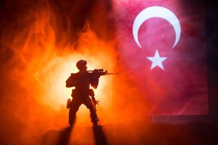 Turkish army concept. Silhouette of armed soldier against a Turkish flag. Creative artwork decoration. Military silhouettes fighting scene dark toned foggy background. Selective focus Banque d'images