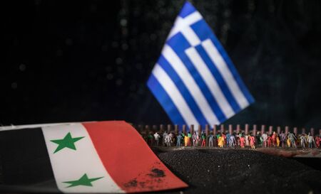 Creative scale decoration. Syrian refugees (crowd) looking on Greece flag standing on border. Concept of crisis of war. Selective focus Stock Photo